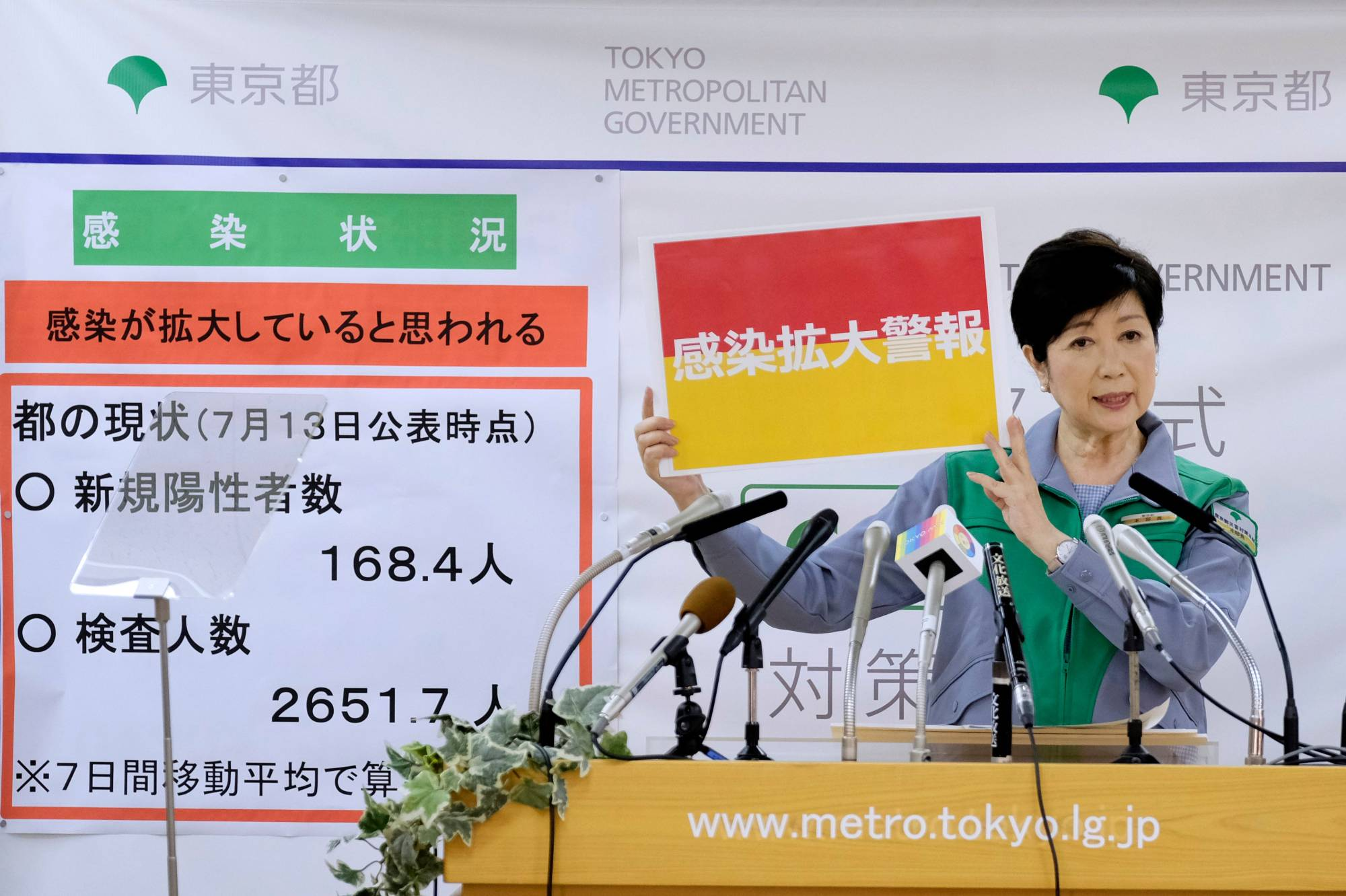 Tokyo Gov. Yuriko Koike displays a sign reading 'Infection spread alert' as she speaks during a news conference Wednesday. | AFP-JIJI