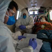 A COVID-19 patient receives medical care on a plane equipped as an ICU unit on the way to Santarem, Brazil, on Wednesday.    AFP-JIJI