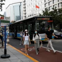 People get off a bus during morning rush hour at the Financial Street area in Beijing on Thursday. | REUTERS