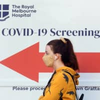 A woman queues outside a COVID-19 coronavirus testing site in Melbourne on Thursday. | AFP-JIJI