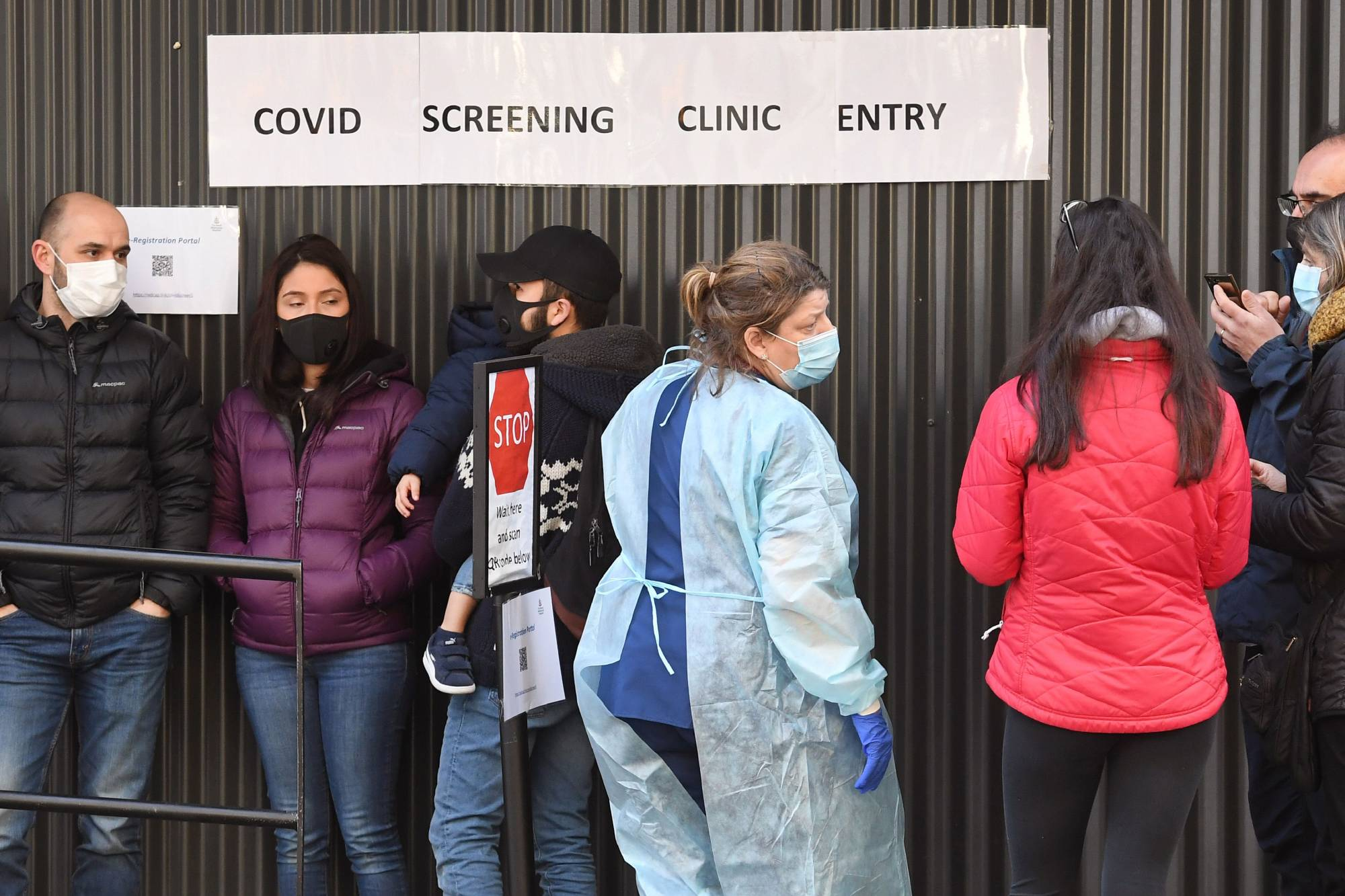 A medical worker speaks to people lined up outside a COVID-19 coronavirus testing venue in Melbourne on Thursday. | AFP-JIJI