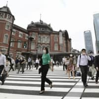 Commuters head to work in central Tokyo on Thursday. | KYODO
