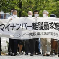 Plaintiffs in a lawsuit seeking to opt out of the My Number personal identification system enter the Kanazawa District Court in Ishikawa Prefecture on June 6. | KYODO