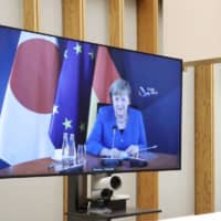 Prime Minister Shinzo Abe holds a teleconference with German Chancellor Angela Merkel at the Prime Minister's Office on Thursday. | CABINET PUBLIC RELATIONS OFFICE / VIA KYODO