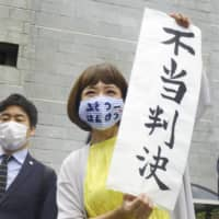 Megumi Igarashi, who works under the pseudonym 'Rokudenashiko,' holds up a sign saying 'unjust ruling' in front of the Supreme Court building Thursday.   KYODO
