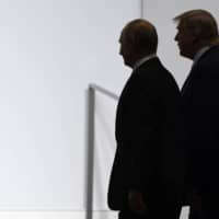 U.S. President Donald Trump and Russian President Vladimir Putin walk together in Osaka in June 2019.  | AP
