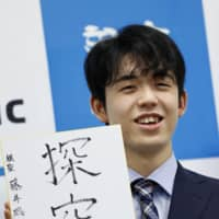 Sota Fujii holds up a piece of paper where he wrote 'tankyu,' meaning pursuit, at a news conference held in Osaka Friday, a day after he became the youngest shogi player ever to win one of the board game's eight major titles. | KYODO