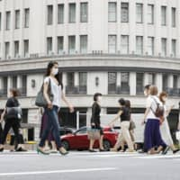 People cross a street in Tokyo's Ginza district on Thursday, when the capital reported a daily record-high of 286 infections. On Friday, Tokyo confirmed 293 cases.   KYODO