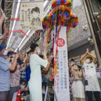 People celebrate at a shopping arcade in Seto, Aichi Prefecture, Thursday after Sota Fujii, a Seto native, became the youngest shogi player ever to win one of the board game's eight major titles. | KYODO