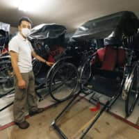 Masao Usui, 39, who pulls a tourist rickshaw in Tokyo's Asakusa district, speaks to the media Friday about his disappointment toward the government's decision to exclude Tokyo from its Go To Travel tourism promotion campaign. | KYODO