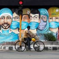 A man rides his bicycle past graffiti amid the spread of the new coronavirus in New Delhi on Friday. | REUTERS