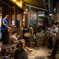 People wearing protective masks wait for their take-out orders at a restaurant in the Soho nightlife area of Hong Kong on Friday. | BLOOMBERG