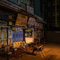 A person sits in front of a shuttered bar at Lan Kwai Fong in the Central district of Hong Kong on Friday. | BLOOMBERG