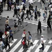 People walk acrss the famed scramble crossing in Tokyo's Shibuya Ward. The Tokyo Metropolitan Government reported 290 cases of COVID-19 on Saturday, keeping the daily figure over 200 for the third day in a row. | AP