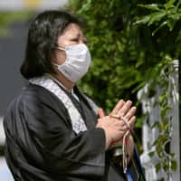 A Buddhist priestess prays near the site of the Kyoto Animation Co. studio in the city on Saturday, the one-year anniversary of a deadly arson attack that left 36 employees dead. | KYODO