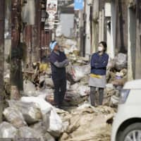 Garbage and debris sits piled up in Hitoyoshi, Kumamoto Prefecture, on Saturday after torrential rains and floods hit the area recently. | KYODO
