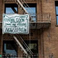 A banner protesting the presence of federal law enforcement officers is displayed in downtown Portland on Friday.  | REUTERS