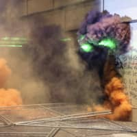 Smoke fills the street as police respond to protesters in Portland on Friday.  | THE OREGONIAN / VIA AP