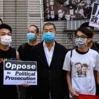 Millionaire media tycoon Jimmy Lai (center), joined by supporters and activists who led a June 4 candlelight vigil commemorating the 1989 Tiananmen Square crackdown in Beijing, gather before a court hearing in Hong Kong on July 13. | AFP-JIJI