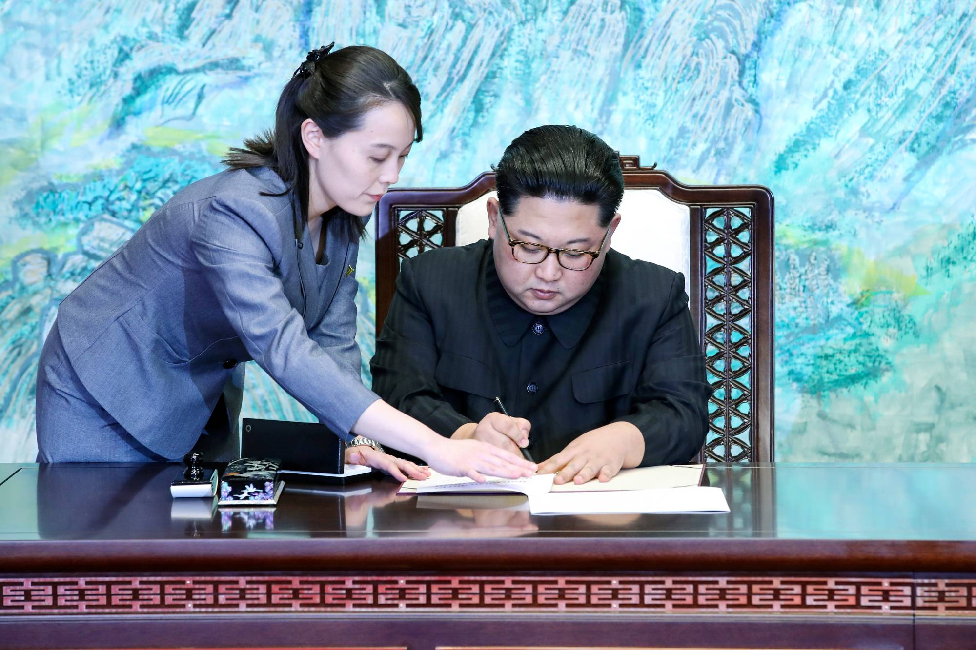 North Korean leader Kim Jong Un is assisted by his sister, Kim Yo Jong, as he signs documents at the truce village of Panmunjom, South Korea, inside the Demilitarized Zone separating the two Koreas in April 2018. | KOREA SUMMIT PRESS POOL / VIA REUTERS