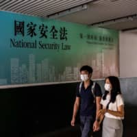 A couple walks past a government advertisement promoting Chinas new national security law in Hong Kong on Saturday. | AFP-JIJI