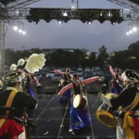 Dancers perform during a drive-in concert at Gyeongbok Palace parking lot in Seoul on Friday. Older children are more likely to spread COVID-19 within a household than younger children and adults, according to a new study of 5,706 coronavirus patients in South Korea. | AP