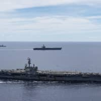 The USS Ronald Reagan (front) and USS Nimitz Carrier Strike Groups sail together in formation in the disputed South China Sea on July 6. | U.S. NAVY / VIA AP