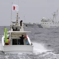 A Japanese fishing vessel sails in waters near the Japanese-controlled, Chinese-claimed Senkaku Islands in the East China Sea as a Chinese government vessel is seen in the background in May 2013.  | KYODO