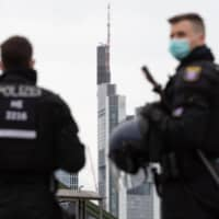 Police officers observe a rally against restrictions put in place to limit the spread of the COVID-19 pandemic in Frankfurt am Main, Germany, in May. Thirty-nine people were detained after police were attacked with a hail of bottles at an open-air party in the city attended by thousands of youngsters Sunday. Five officers were injured in the riot.   AFP-JIJI