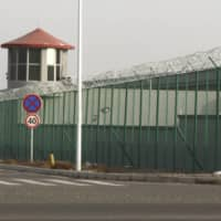 A guard tower and barbed wire fence surround a detention facility in China's Xinjiang region in December 2018. Britain on Sunday accused Beijing of 'gross, egregious human rights abuses' over its 'deeply troubling' treatment of ethnic and religious minorities in the western region.    AP