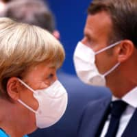 Germany's Chancellor Angela Merkel and France's President Emmanuel Macron attend an EU summit at the European Council building in Brussels on Saturday as the leaders of the European Union hold their first face-to-face summit over a post-virus economic rescue plan. | POOL / VIA AFP-JIJI
