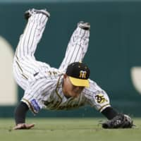 Tigers outfielder Kosuke Fukudome makes a diving catch during the first inning on Sunday at Koshien Stadium. | KYODO