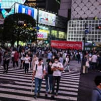 People wearing face masks cross a crowded intersection in front of Shibuya Station in Tokyo. The metropolitan government confirmed 168 new cases of COVID-19 infection on Monday. | AFP-JIJI