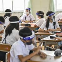 Students wearing face shields in class at an elementary school in the city of Osaka in June. | KYODO