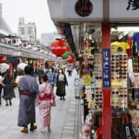 People walk on the Nakamise shopping street in Tokyo's Asakusa district on Friday. | KYODO