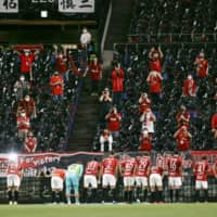 Urawa supporters applaud the team after its win over Kashima on July 12 in Saitama. | KYODO