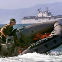 A French peacekeeper patrols the coast of East Timor near Dili in front of the USS Belleau Wood in 1999.   REUTERS