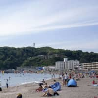 People crowd a beach in Zushi, Kanagawa Prefecture, on June 20, even though its swimming area is closed. | KYODO