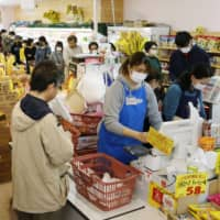 Shoppers purchase groceries at a supermarket in Tokyo in March. | KYODO