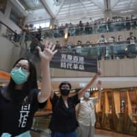 Protesters hold up a banner reading 'Librate Hong Kong, Revolution of out time' and gesture with five fingers, signifying the 'Five demands — not one less,' at a shopping mall in Hong Kong on June 9. The slogan had just been banned by the government under the new legislation, stating that it had separatist connotations. | AP
