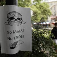 A man wearing a mask to protect against the spread of COVID-19 passes a sign requiring masks at a restaurant on July 7 in San Antonio.  | AP