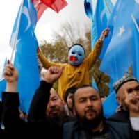 A masked Uighur boy takes part in a protest against China at a mosque in Istanbul in November 2018. The U.S. added 11 Chinese companies implicated in what it called human rights violations in connection with China's treatment of its Uighurs in Xinjiang, China, to the U.S. economic blacklist. | REUTERS