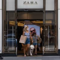 Shoppers exit a Zara clothing store in the Central district of Hong Kong on Sunday. | BLOOMBERG