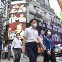 The head of Shinjuku ward, Yoshizumi Kenichi (center), asks for cooperation with measures against the pandemic in the Kabukicho district on Monday. | KYODO