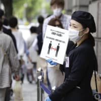 An employee holds a board reminding customers to maintain social distancing at the entrance of a department store in Kobe on May 22.   KYODO
