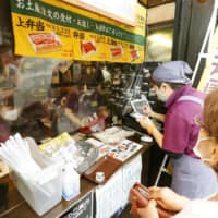 A woman pays for takeout broiled eel at a restaurant in the city of Narita, near Tokyo, on Tuesday, the Day of the Ox, when eel is traditionally eaten in Japan. | KYODO
