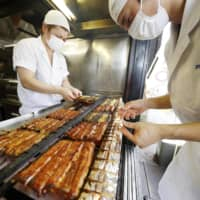 Chefs cook eel at a restaurant in the city of Narita, near Tokyo, on Tuesday, the Day of the Ox, when eel is traditionally eaten in Japan. | KYODO