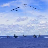 The USS Ronald Reagan Carrier Strike Group and units from the Maritime Self-Defense Force and Australian Defence Force participate in trilateral military exercises in the Philippine Sea on Tuesday. | U.S. NAVY