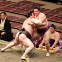 Hakuho (left) drives Endo out of the ring during their bout on Day 3 of the July Grand Sumo Tournament on Tuesday at Ryogoku Kokugikan. | NIKKAN SPORTS