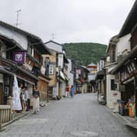 Souvenir shops are seen open near Kiyomizu Temple in the city of Kyoto last week, but few visitors are present. | KYODO